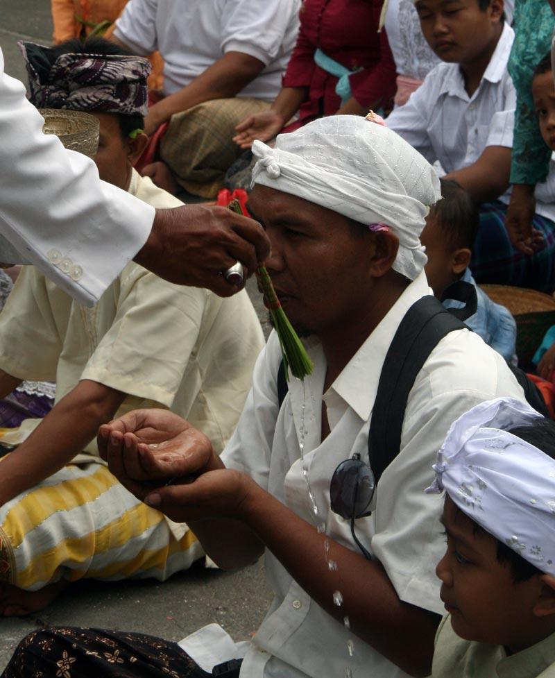 מאמינים מקבלים מים קדושים במקדש באלינזי | צילום: ניסו קדם