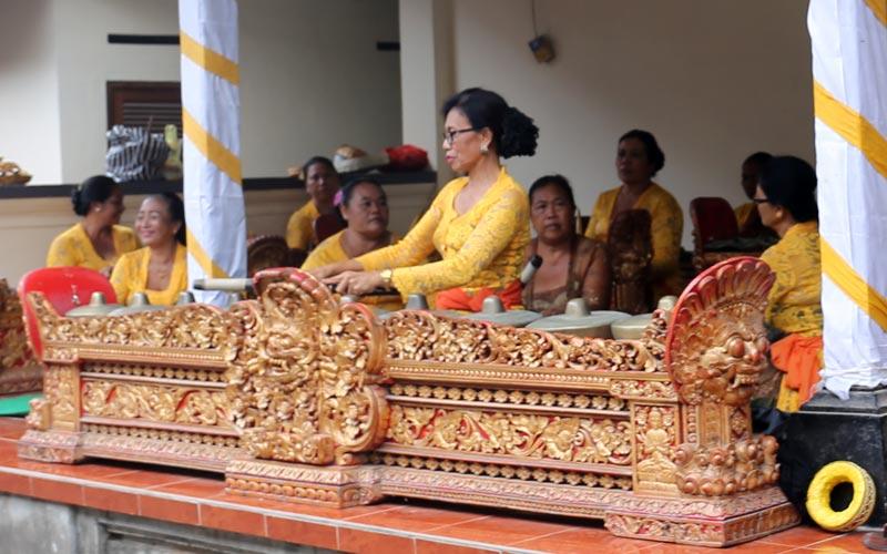 אשה מנגנת על בונאנג (bonang) - סט של גונגים אופקיים - בתזמורת גמאלאן חלוצית של נשים. באלי, אינדונזיה. צילום: ניסו קדם